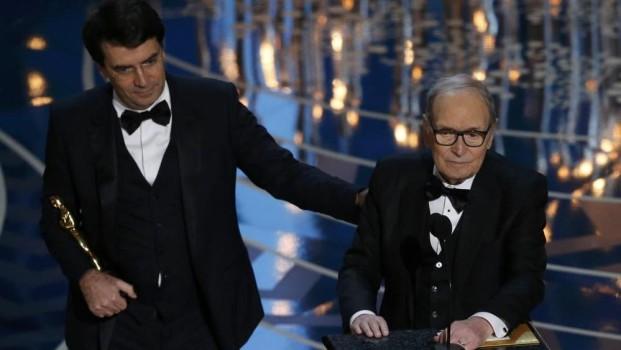 Ennio Morricone (a destra) sul palco del Dolby Theatre ha ricevuto l'Oscar 2016