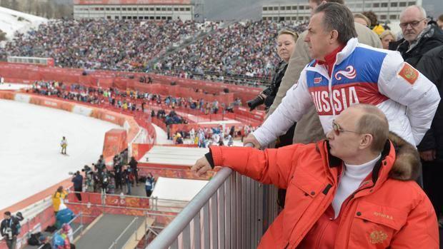 Il presidente russo Vladimir Putin (seduto) e il ministro dello Sport Vitaly Mutko