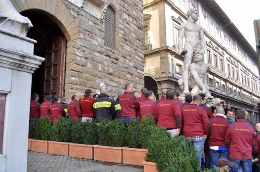 Un gruppo di Vigili del Fuoco volta le spalle