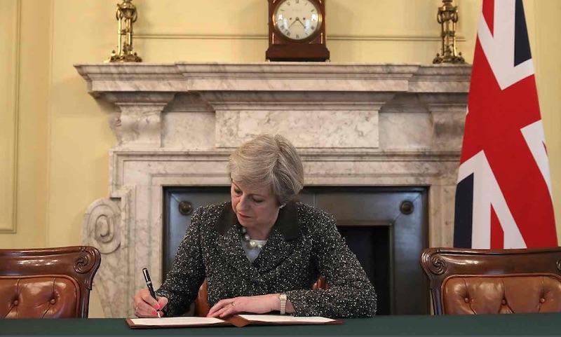 La premier inglese Theresa May firma la lettera della Brexit