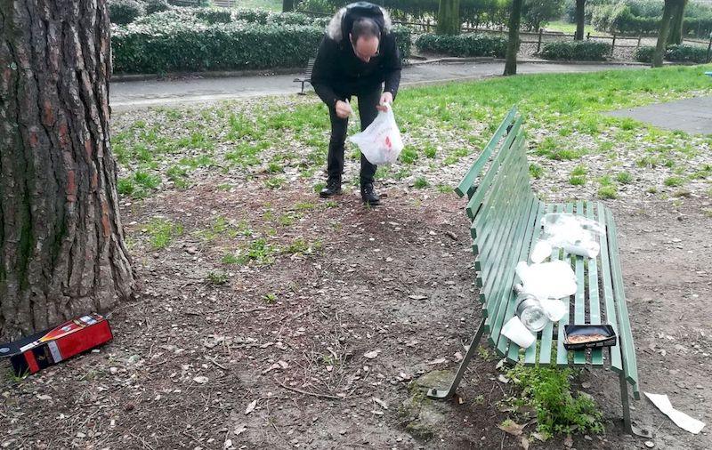 Un cittadino raccoglie i rifiuti abbandonati sulle panchine della Montagnola (foto Francesco Martinucci)