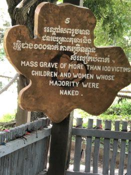 Un cartello indica una fossa comune dove furono trovati i corpi nudi di donne e bambini