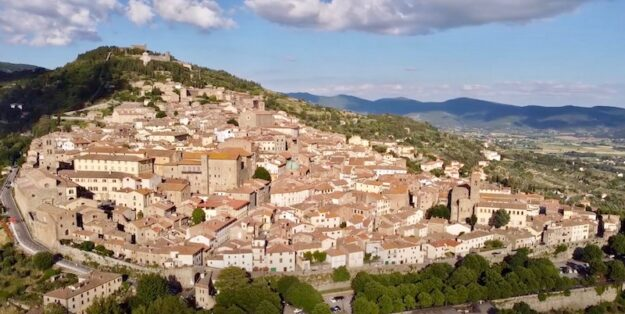 La città di Cortona distesa sulla collina (Foto da frame video Cortona Social Media)
