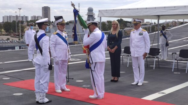 L'ammiraglio Credendino bacia la bandiera della Marina e delle Forze Navali appena ricevuta dall'ammiraglio Treu
